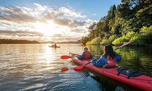 People kayaking in Rotorua in the late afternoon